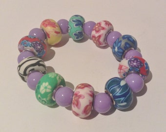 Bracelet 18cm. Features multi coloured and multi floral patterned Rondel Clay beads. Mauve Enamelled Glass round beads