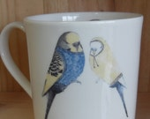 We go together like budgies in knitwear- two budgies in jumpers pint sized Bone China mug with ceramic tranfer