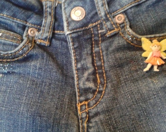 Little girls embellished jeans.  Hand painted flowers and hearts adorn these blue jeans along with some cute girly buttons and glitter.