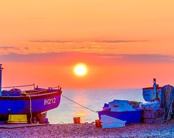 Sunrise at Aldeburgh. A fine art photographic Giclée print of the sun rising between two beached fishing boats on Aldeburgh beach.
