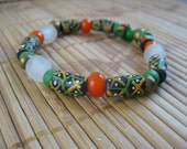 Ghana trade bead bracelet with white recycled glass beads, orange white heart beads, green Padre beads, and Ethiopian brass beads