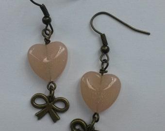 Classic bronze earrings with a light peachy heart, peach earrings, and a bow charm