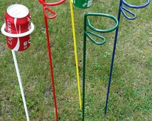 Drink holder. Fire pit, Lawn. Outdoors. Camping. Pop Can Holder. Beer. Yard. Metal. Powder coated. Blue. White. Red. Green. Yellow.