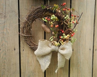 Fall wreath with berries, leaves, pine cones, and a burlap bow.