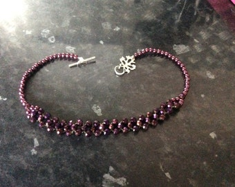 """Handmade 15"""" plum coloured glass beaded necklace finished with a silver coloured leaf toggle clasp"""