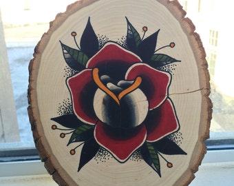 Rose tattoo design on a wood slice.
