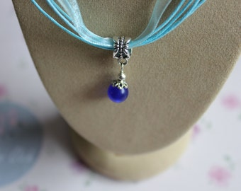 A pale blue ribbon necklace with a deep blue pendant