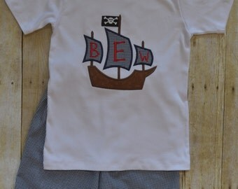 Gingham shorts with monogrammed pirate ship appliqué.