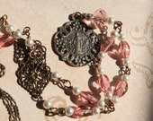 Bronze St. Mary medal with pink and pearl beaded chain