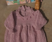 Romper/onesie/all in one outfit for a baby girl age 3-9 months. Hand knitted in pale pink, the pattern is suitable for Baptisms/blessings