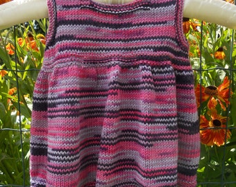 """Dress/pinafore/tunic top for a baby girl, hand knitted in shades of pink, lilac and purple, chest 18-19"""", approx age 6-12 months."""