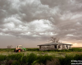 Tractor & abandoned house beneath stormy sky in Levelland, Texas