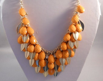 3 Row Bib Necklace with Orange Teardrop Beads, Gold Tone Leaves and Clear Rhinestones on a Gold Tone Chain