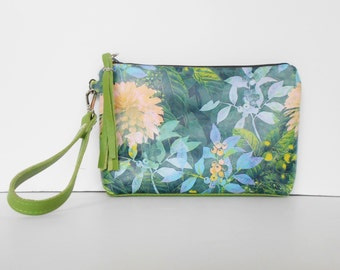 Leather clutch, leather wristlet with floral print and green trim.