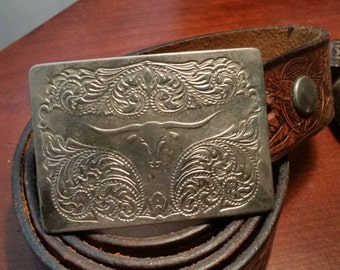 Vintage tooled leather belt with silvertone embossed bull's head removable buckle.