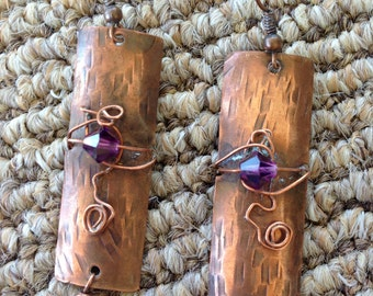 Hand forged copper earrings with deep purple crystals