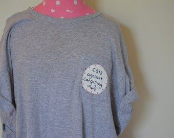 "grey ""cats against catcalling"" tee shirt"