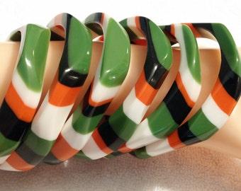 Thin vertical green, orange, black, white striped Lucite bangle bracelet