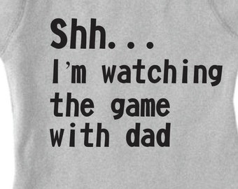 "Baby onesie that says ""Shh... I'm watching the game with dad."""