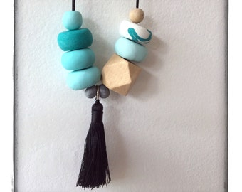 Ombre mint beaded necklace with wooden accent beads and black tassel.