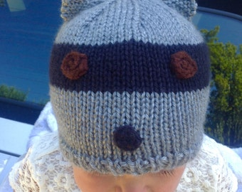 Darling hand knit raccoon hat for your favorite child! Hat has a tail in the back.