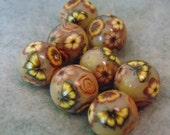 foiled and round polymer clay beads with flowers and butterfly