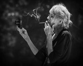 The photographer, a gray haired woman smoking with camera, black white portrait, humorous original fine art print, black white, low light