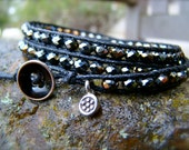 Wrap bracelet handmade with black iris fire polished rondelle beads and a thai silver charm on a black waxed cotton cord