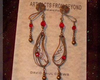 "Wire wrapped chandelier earrings in brass with clear and ruby glass beads titled ""Paisley Cosmos"""