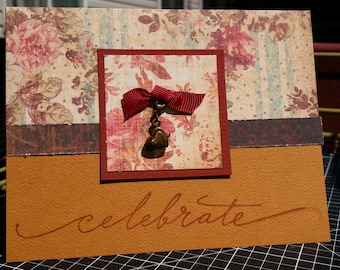 Beautiful Handmade Card for any Celebration. Includes the word Celebrate written in a cursive font and a brass heart charm.