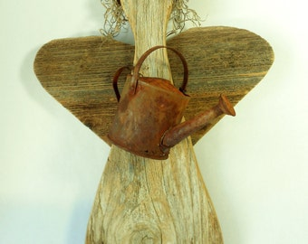 Garden Angel of weathered wood with a rusty watering can, grapevine halo