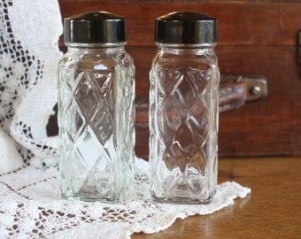 Vintage salt and pepper shakers - pressed glass with bakelite lid