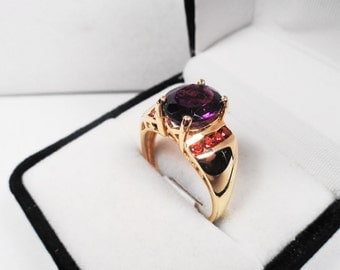 Amethyst Ring.Oval in a 14 kt. Gold Ring with Garnet Accents.