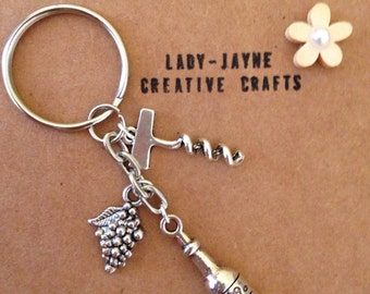 Silver-plated wine lovers charm keyring. Wine bottle, grapes and cork screw charms. Suitable for house/car keys. Novelty gift.