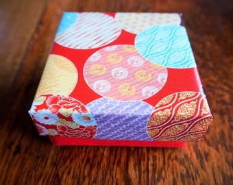 Red origami gift box in a colourful ball design with lid