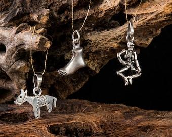 Five different silver miracles pendants, donkey, skeleton, foot, bird feather, hummingbird