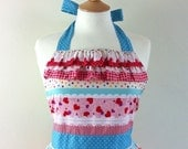 Retro apron with ruffles, vintage style pink, red and blue pattern on a white fabric.