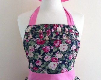 Retro apron with ruffles, pink and cream floral pattern on a dark blue fabric, fully lined.