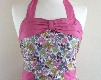 Retro apron with bow, eartht coloured leaves on a white fabric.