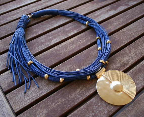 Amazing multilayer multistrand leather necklace with a gold plated pendant and gold plated metallic tubes