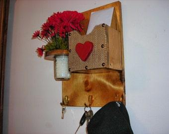 Mail sorter with key hooks, jar for floral decorations.