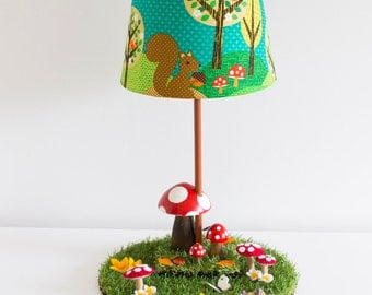 Woodland nursery toadstool lamp with squirrel shade in green, teal and autumn colours.