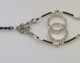 Women, black leather strap, and black and silver chains with interlocking rings rhinestone bracelet