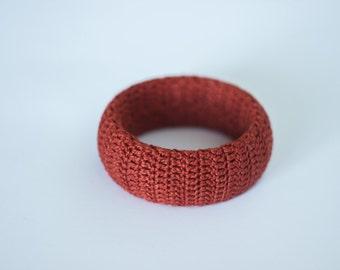 Bracelet. Red (terracotta) bracelet decorated with knitted threads. Black bracelet