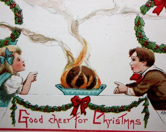 Vintage Christmas Postcard Embossed with two children eating Christmas dinner at the table with wreath by L & E Artist signed HBG 1913