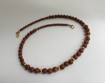 Necklace of Goldstone graduated round beads with brass donut spacers.  G56