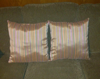 Showy, elegant pillows in rich shades of gold, green, hot pink and lavender make a decor statement in any home