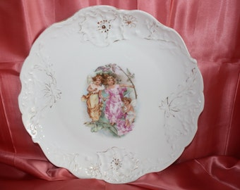 """Antique 12"""" porcelain charger with transfer of 3 young angels, possibly Limoges"""