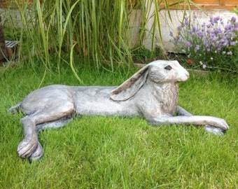 large stone lying hare. Garden sculpture. Large outdoor sculpture