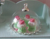 4 pretty cupcakes with plate and glass dome